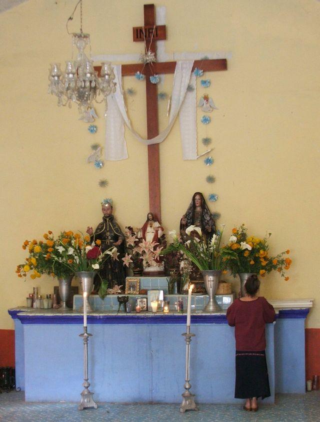 Susanna Starr placing photo on Altar, Cemetery Chapel - Day of the Dead - Oaxaca State, Mexico ©John Lamkin