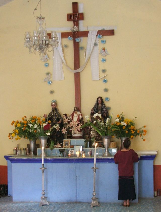 Susanna Starr placing photo on Altar, Cemetery Chapel - Day of the Dead - Oaxaca State, Mexico ©John Lamkin